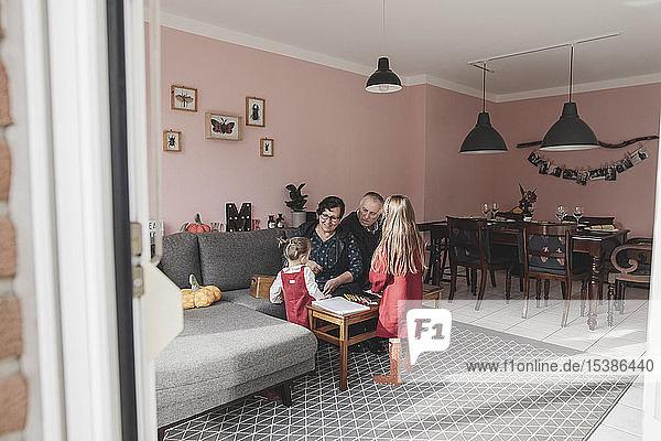 Zwei Mädchen spielen zu Hause im Wohnzimmer mit ihren Großeltern