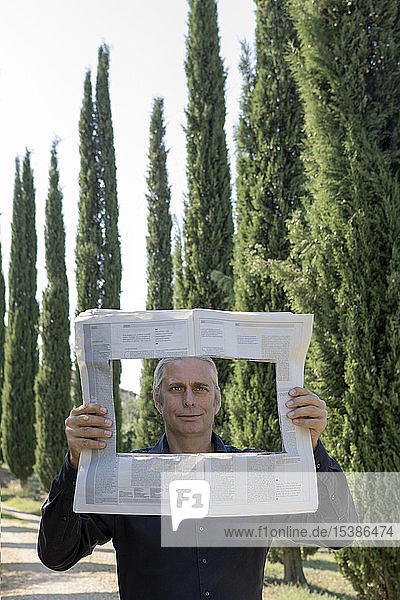Italy  Tuscany  man surrounded by cypresses reading newspaper with a hole