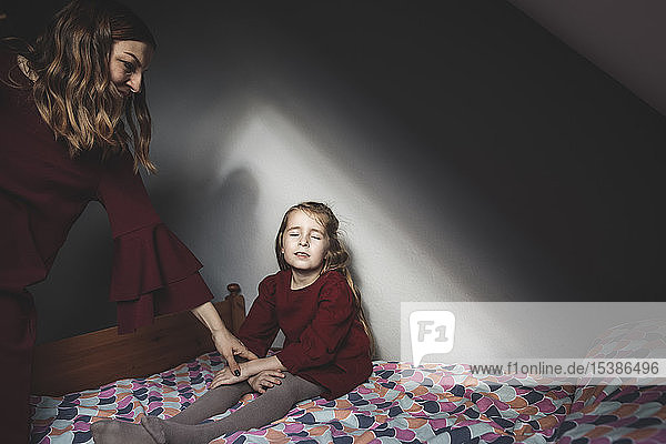 Mother with daughter sitting on bed at home with closed eyes