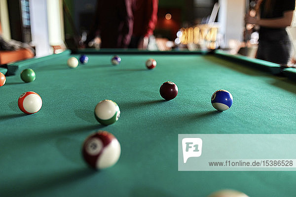 Billiard balls on table with people in background