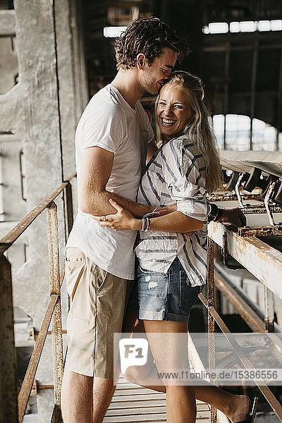 Glückliches junges Paar umarmt sich in einem alten Bahnhof
