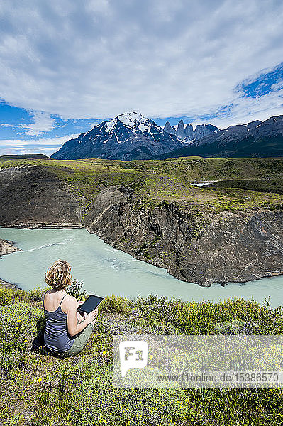 Chile  Patagonia  woman using tablet at a river bend in Torres del Paine National Park
