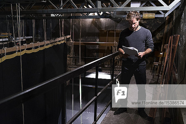 Actor at theatre studying script backstage
