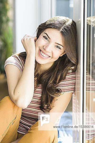Portrait of smiling young woman sitting at the window at home