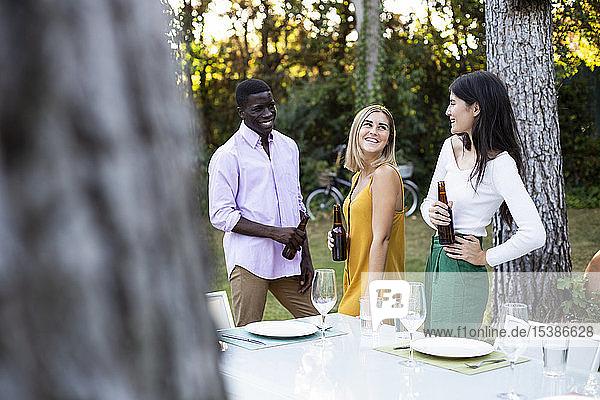 Freunde trinken Bier bei einem sommerlichen Abendessen im Garten