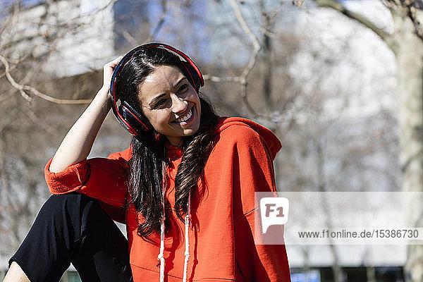 Junge zeitgenössische Tänzerin mit rotem Kapuzenhemd  die sitzt und Musik hört