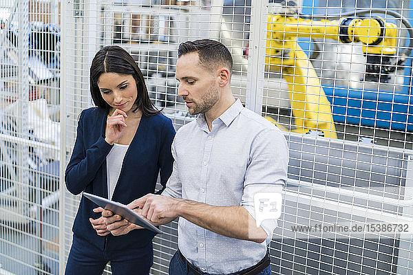 Geschäftsmann und Geschäftsfrau mit Tablettengespräch in moderner Fabrik