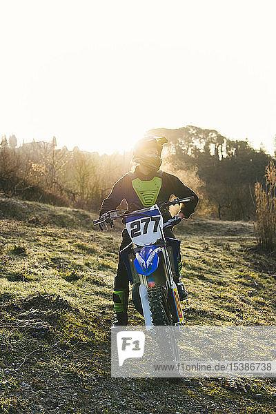 Motocross-Fahrer steht bei Sonnenuntergang auf der Rennstrecke