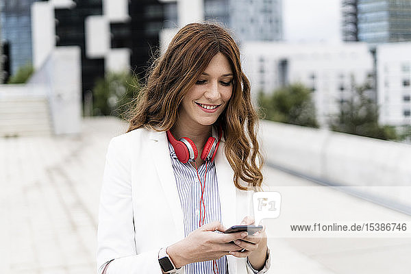 Young businesswoman commuting in the city  using smartphone