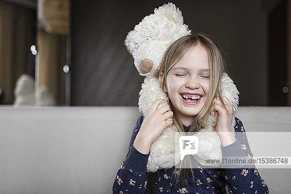Portrait of laughing little girl with tooth gap holding white teddy bear