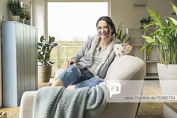 Portrait of happy woman with a mug and tablet sitting on the couch at home