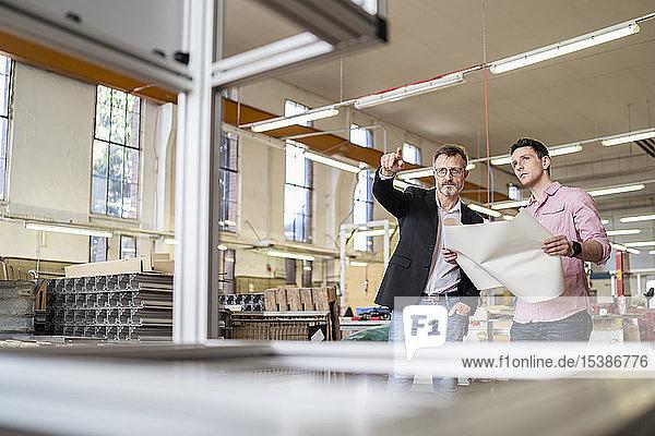 Zwei Männer besprechen Plan in einer Fabrik