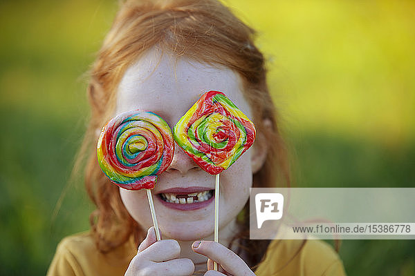 Happy girl covering her eyes with lollipops