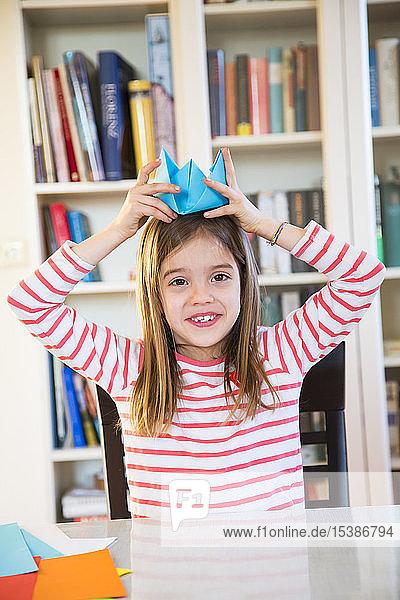 Porträt eines lächelnden Mädchens  das sich zu Hause einen selbst gebastelten Papierhut aufsetzt
