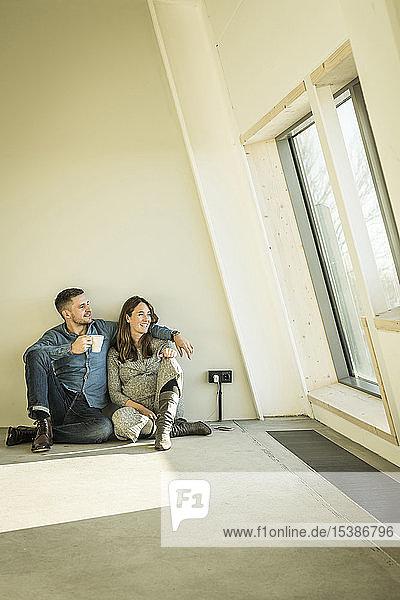 glückliches Paar  ein Baby erwartend  auf dem Boden ihrer neuen Wohnung sitzend