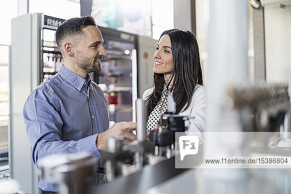 Lächelnder Geschäftsmann und Geschäftsfrau im Gespräch an einer Maschine in einer modernen Fabrik