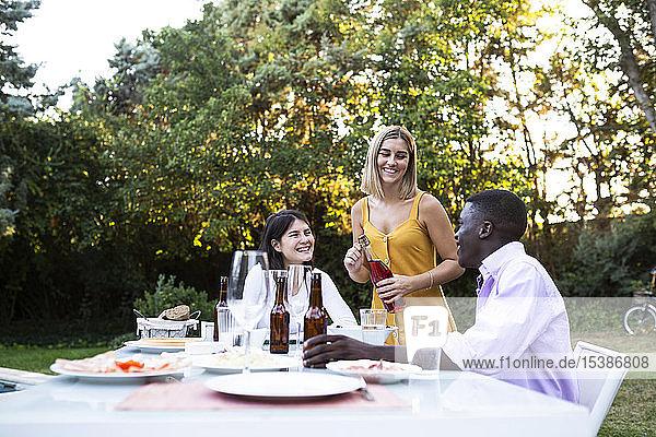Freunde bei einem Sommeressen im Garten beim Öffnen einer Flasche Wein