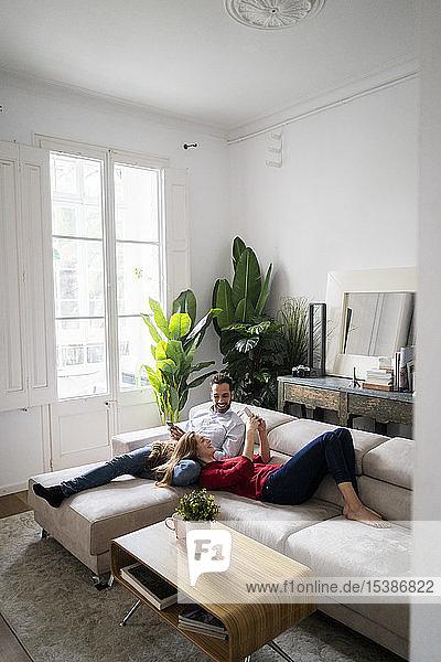 Auf dem Sofa liegendes Ehepaar mit Erben-Smartphones