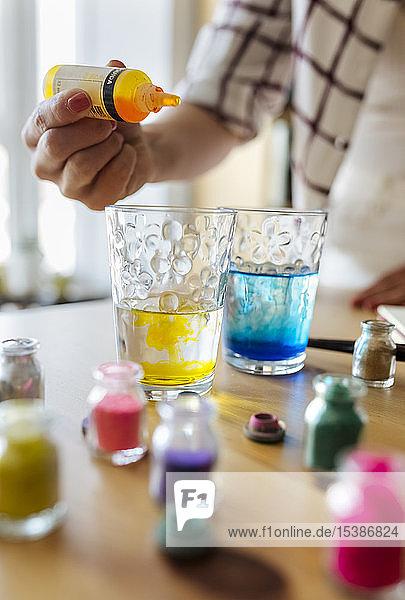 Maler  der flüssige Farbe in ein Glas Wasser füllt  Teilansicht