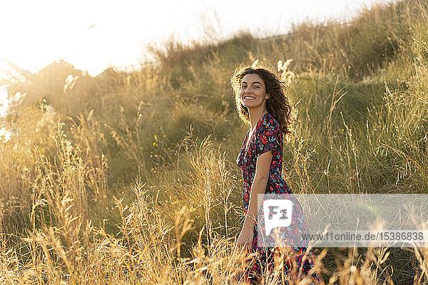 Glückliche junge Frau steht auf der Sommerwiese