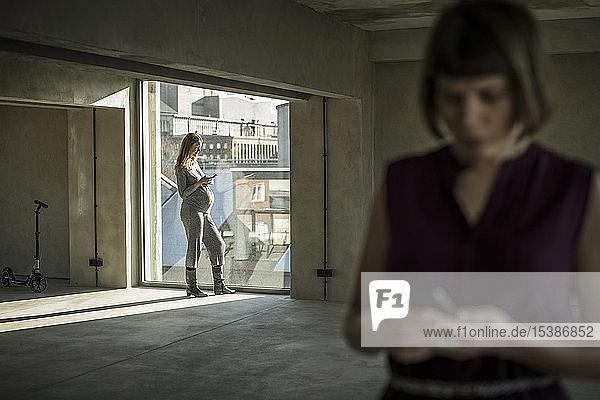 Zwei Geschäftsfrauen überprüfen Nachrichten auf ihren Smartphones