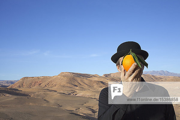Morocco  Ounila Valley  man wearing a bowler hat holding an orange in front of his face