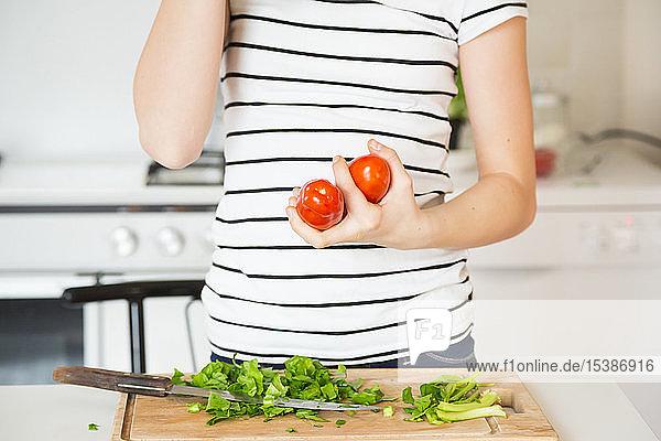 Mädchen steht in der Küche und hält Tomaten  Teilansicht