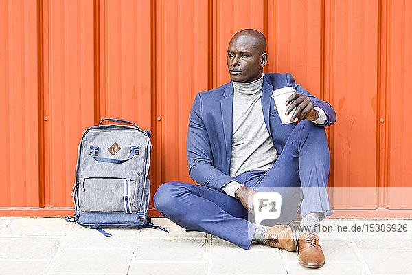 Modischer Geschäftsmann sitzt vor orangener Wand und trinkt Kaffee zum Mitnehmen