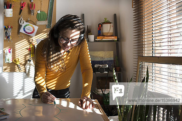 Frau malt eine Katze und hört Musik