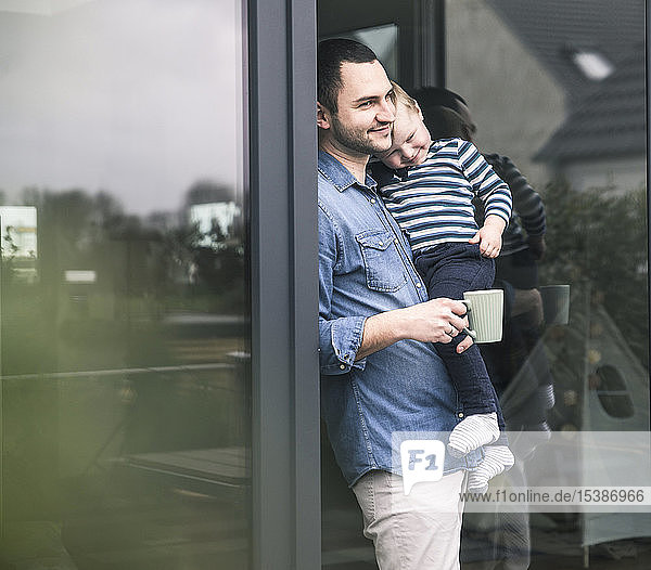Father with cup of coffee carrying son at terrace door at home