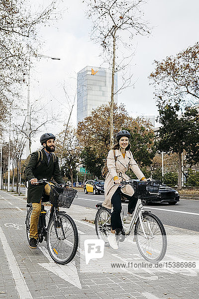 Ein Paar fährt in der Stadt auf dem Fahrradweg E-Bikes