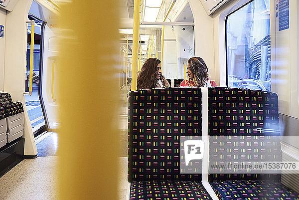 UK  London  two women talking in underground train