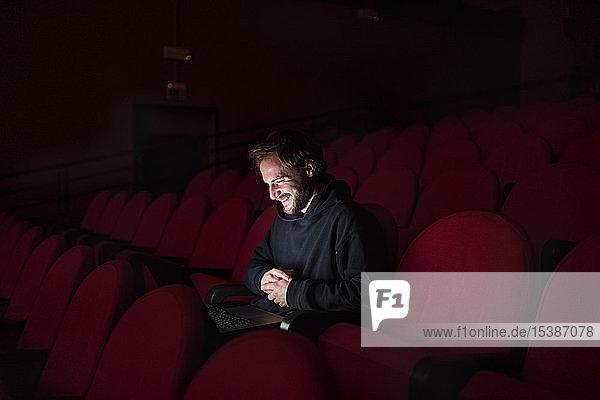 Lachender Regisseur sitzend bei Lachender Regisseur sitzend bei