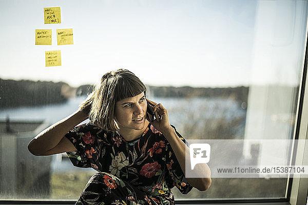 Kreative Geschäftsfrau sitzt am Windoe und telefoniert