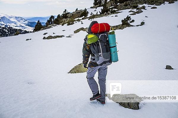 Rückansicht eines Mannes mit Rucksack,  schneebedeckte Berge
