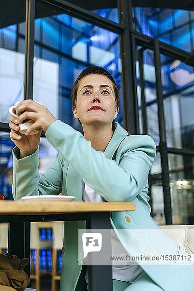 Frau in Bar mit Tasse Kaffee
