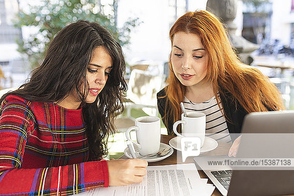 Woman signing contract at pavement cafe