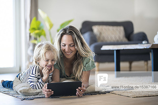 Smiling mother and son lying on the floor at home using tablet