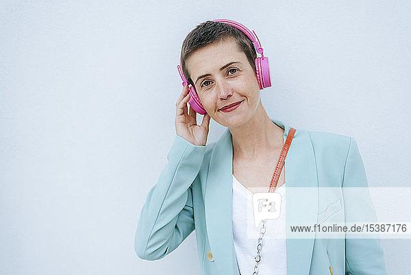 Frau in Jacke  die Musik hört  rosa Kopfhörer
