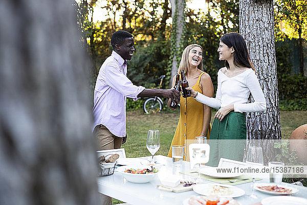 Freunde stoßen bei einem sommerlichen Abendessen im Garten mit Bier an