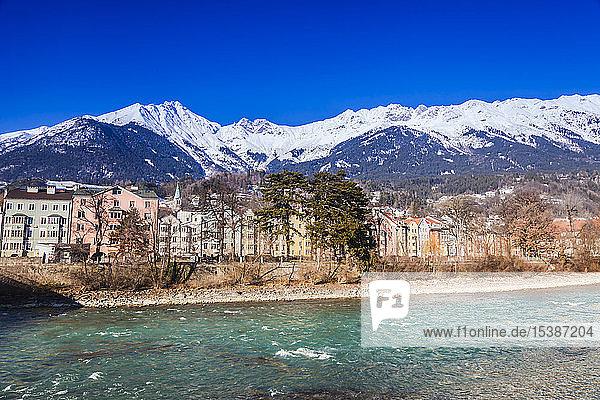Österreich  Tirol  Innsbruck  farbige Gebäude entlang des Inns mit schneebedeckten Alpen im Hintergrund