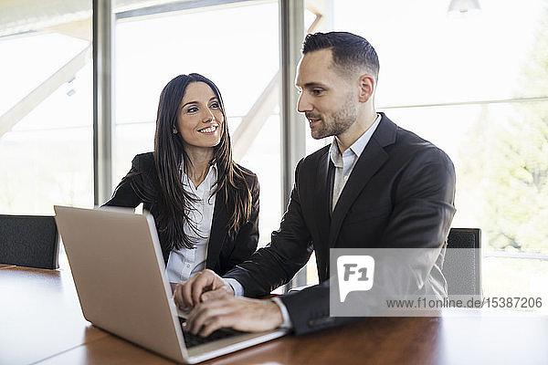 Lächelnde Geschäftsfrau und Geschäftsmann mit Laptop arbeiten im Büro