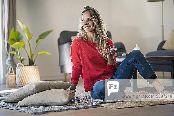 Lächelnde Frau sitzt zu Hause auf dem Boden und hält ein Handy in der Hand