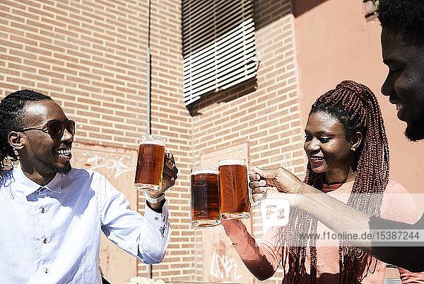 Drei glückliche Freunde trinken Bier in einer Bar im Freien