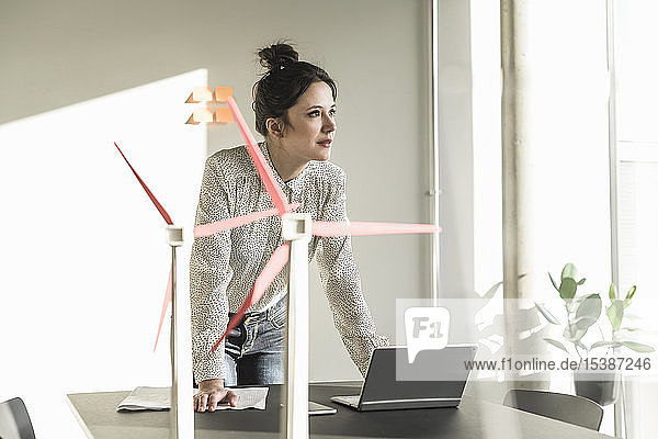 Businesswoman with wind turbine models and laptop on desk in office
