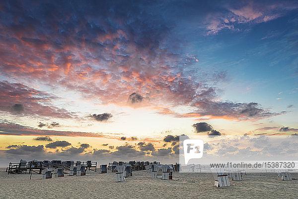 Deutschland  Sankt Peter Ording  Kapuzenstrandkörbe am Strand im Sonnenuntergang