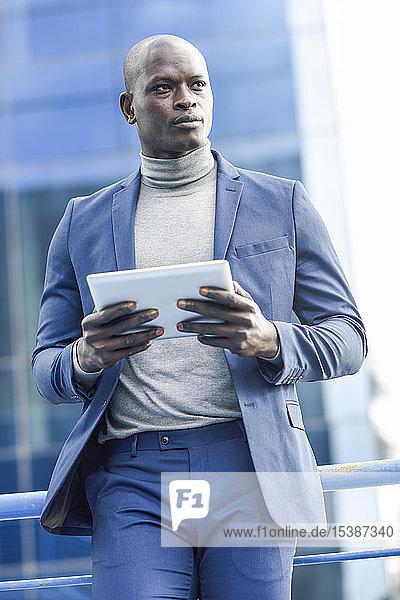 Porträt eines klugen Geschäftsmannes im blauen Anzug mit digitalem Tablet im Freien