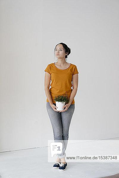 Junge Frau steht an einer Wand und hält eine Topfpflanze