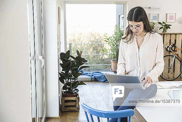 Young woman sitting on table at home using laptop