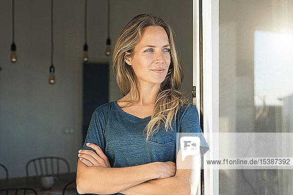 Frau lehnt zu Hause am offenen Fenster und schaut zur Seite